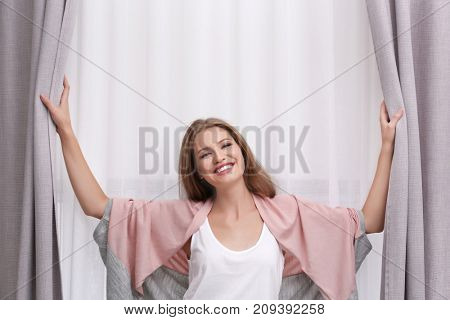 Young woman standing near curtains at home