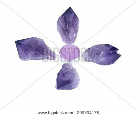 Lavender tea light surrounded by amethyst points isolated on white background