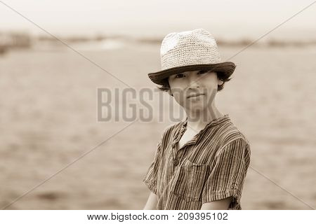 Portrait of a beautiful boy in a short jacket and a hat on a background of the sea. Sepia.