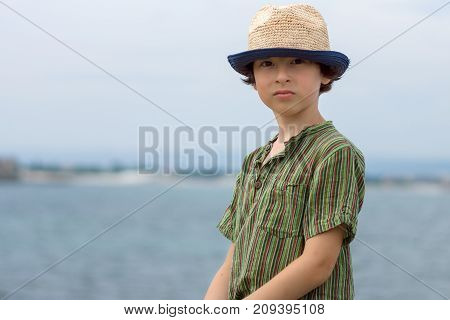 Portrait of a beautiful boy in a short jacket and a hat on a background of the sea.