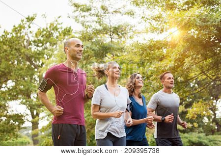 Runners team on morning training together. Group of mature athletes running outside in the park. Group of senior healthy people running outdoor and doing fitness exercises in summer.