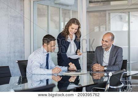 Smiling business team working together on a project in a modern conference room. Happy business partners planning work at meeting. Successful business people group working in modern office.