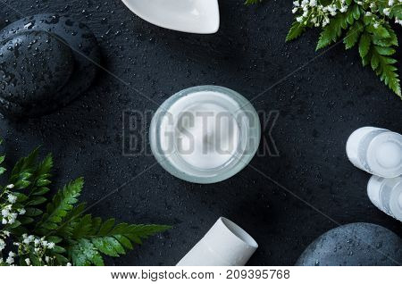 Moisturizer jar with white tubes of lotion and basalt rock on black background. Spa massage cream on wet slate ready for therapy. Natural fresh facial moisturizer in a glass, cosmetic and spa concept.