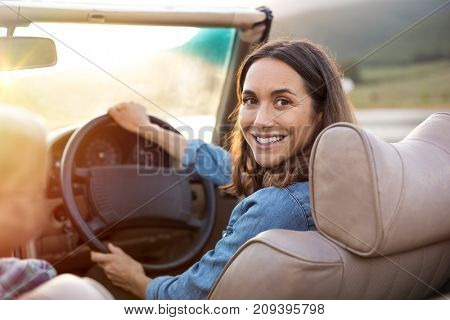 Happy woman holding steering wheel ready to drive and looking back. Smiling mature woman driving convertible car and looking at camera. Carefree woman enjoying driving in a cabriolet.