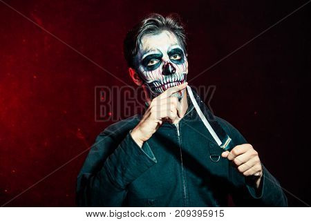 scary halloween skeleton man in jacket hold big knife studio shot closeup