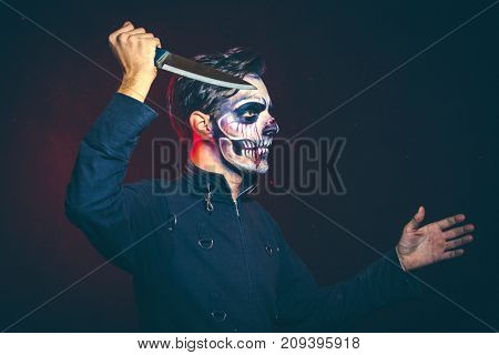 scary halloween skeleton man in jacket with big knife studio shot closeup