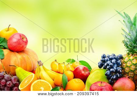 Large collection of fruits and vegetables on blur green background. Copy space.