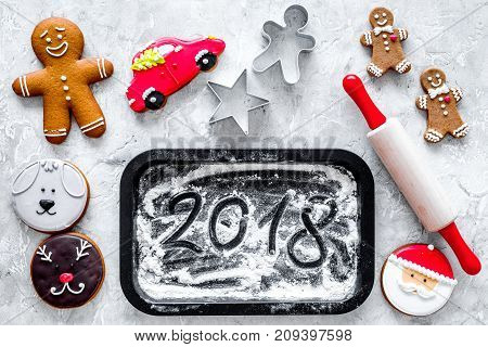 Cook gingerbread for new year 2018. Gingerbread man, rolling pin, flour on stone background top view.