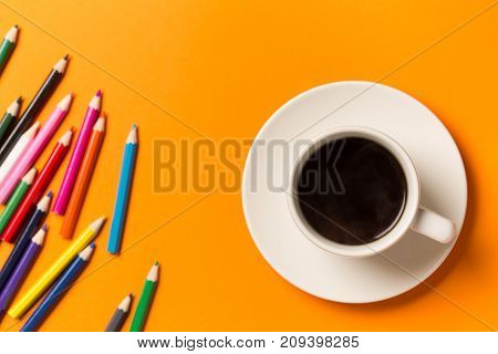 A cup of coffee on orange background. Top view with space for your text.