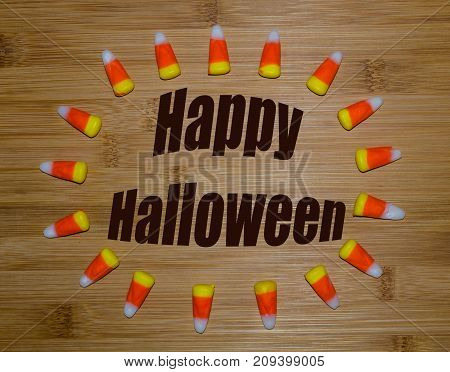 Happy Halloween notice surrounded by sweet candy corn.  Fun festive fall, autumn holiday celebrated with candy and treats.
