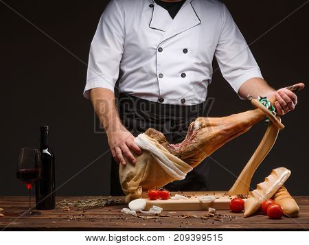 Cook holds a ham in his hands. Spanish jamon, spain traditional bread, tomatoes, spices, onion rings, bottle of red wine and glass with red wine. Horizontal close up image