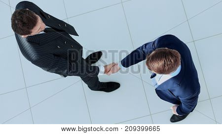 Top view of a two businessman shaking hands - Welcome to business