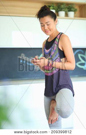 Portrait of a beautiful sports woman using smartphone. Woman. Yoga. Sport
