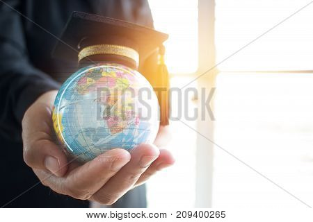Education in Global Graduation cap on Businessman holding Earth globe model ball map with Radar Education in Global Graduation cap on Businessman holding Earth globe model map with Radar background in hands. Concept of global business abroad educational B