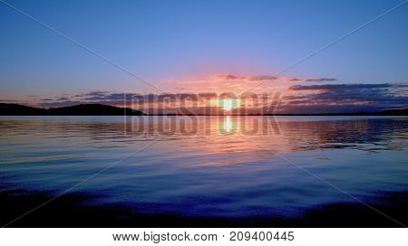 A striking inspirational sunrise photo over tranquil lake water with colorful reflections at dawn Captured on Lake Macquarie New South Wales Australia