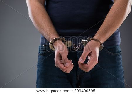Man with his hands handcuffed in criminal concept