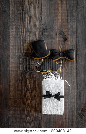 Black tie, mustache and hat cookies on sticks for happy father's day present cookies on wooden background top view space for text