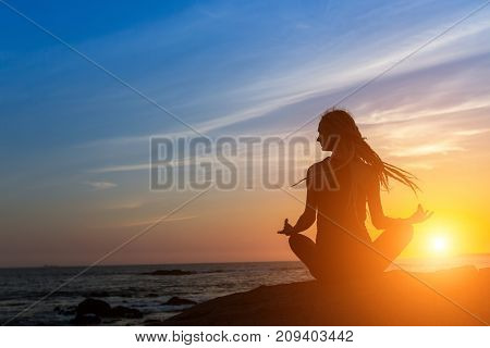 Yoga woman silhouette on the ocean during amazing sunset.