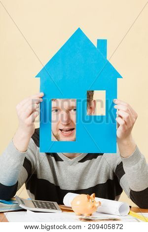 Young Man With Paper Model Of House.