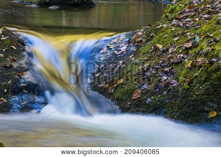 Beautiful colorful flowing water reflecting fall leaves and blue sky nature forest background