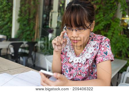 Young student surfing the Internet on her smart phone
