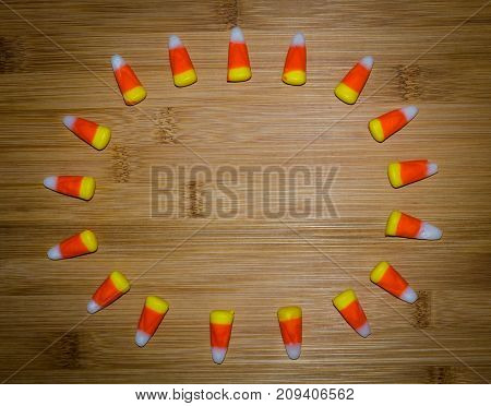 Candy corn frame in circle pattern.  Blank wood space available for message or note.  Celebrate Halloween or festive autumn theme.