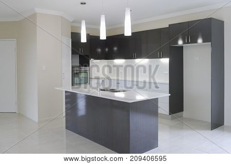 Modern kitchen with overhead lights and island work bench