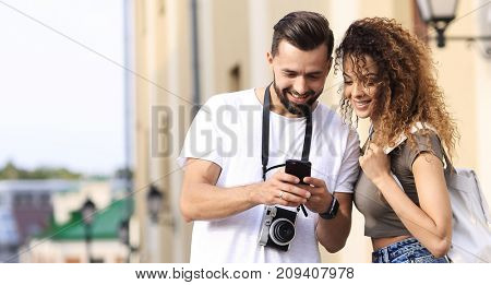 Young couple visiting city in summertime and looking photos