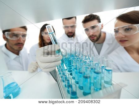 background image is a group of microbiologists studying the liquid in the glass tube.