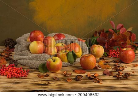 apples with a berry on the table and a bag