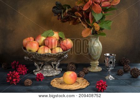 apples in a vase with autumn leaves and apple juice on a table