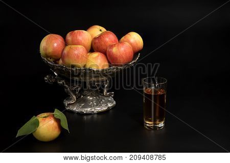 apples with leaves in a vase on a black background
