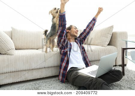 happy guy exults with his dog sitting near the sofa in the living room.