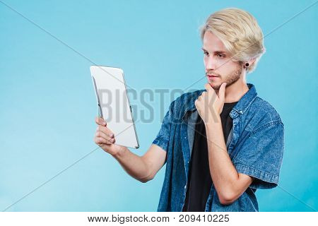 Education social media. Modern technology internet concept. Stylish handsome young man using tablet computer thinking