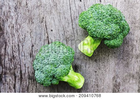 Closeup top view fresh broccoli on wooden background raw food for cooking