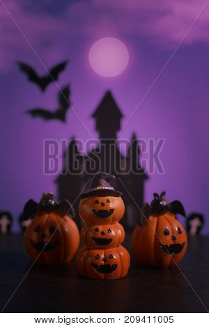 Halloween pumpkins jack-o-lantern on dark purple background. Halloween pumpkin background. Happy Halloween.