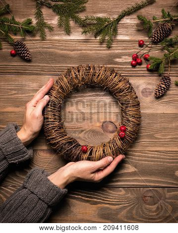 Female hands holding Christmas wreath of fir branches. A traditional symbol of Christmas. The festive concept. The view from the top flat lay. Dark wooden background.