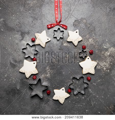 Christmas wreath cookies and various metal shapes on a gray background decorated with a red bow and berries . A traditional symbol of Christmas. The festive concept. The view from the top flat layer. The gray backdrop of concrete. A copy of the places. Sq