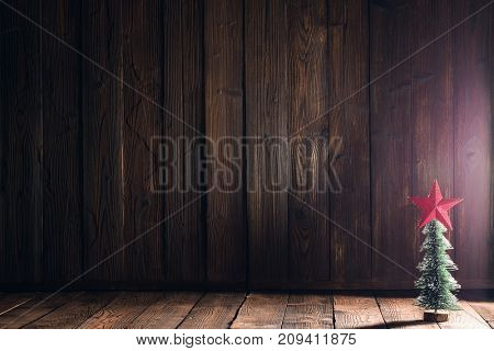 Small decorative Christmas tree on natural wooden background
