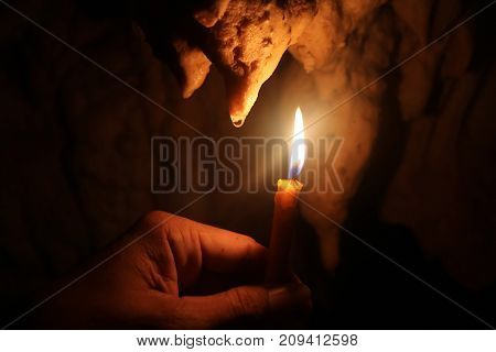 Lighting candles on hand in the limestone caves in Thailand.