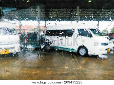 Rain drops on a car window and a view of the street in Thailand.