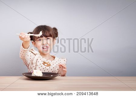 Kids enjoy eating concept : Happy little cute mixed race girl enjoy eating cake with smiley face tongue stick with spoon in her hand for invite to eat
