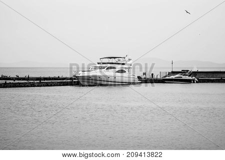 NESEBAR BULGARIA - AUGUST 21 2017: Luxury motor yacht Sunseeker in the seaport at the pier in the UNESCO World Heritage town of Nesebar. Black and white.
