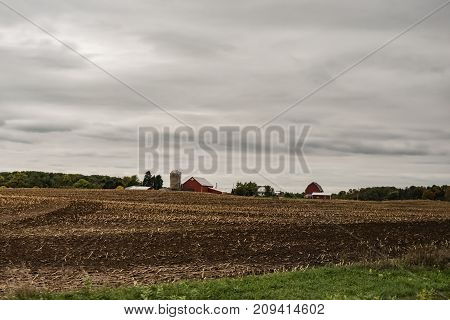 A harvested corn field with red barns and silo of a traditional dairy farm in the background with overcast skies and copy room at top