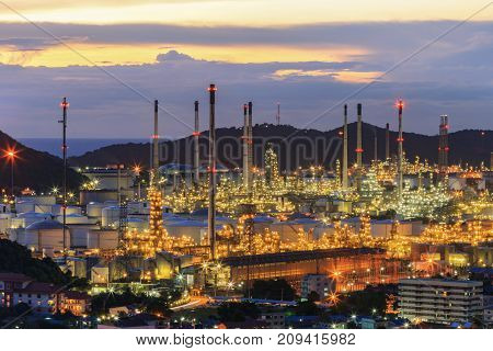 Oil refinery plant and city at twilight .