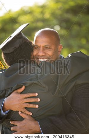 Father hugging his son on his graduation day.