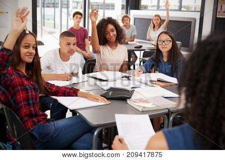 High school kids raise hands, teacher sitting at their desk