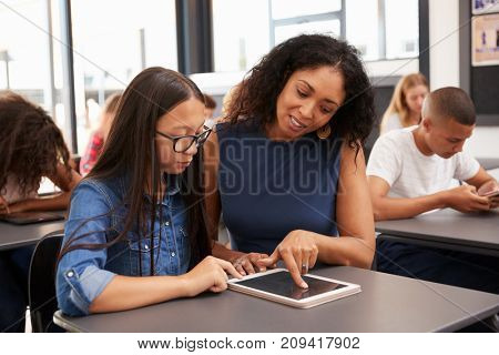 Teacher helping teenage schoolgirl with tablet computer