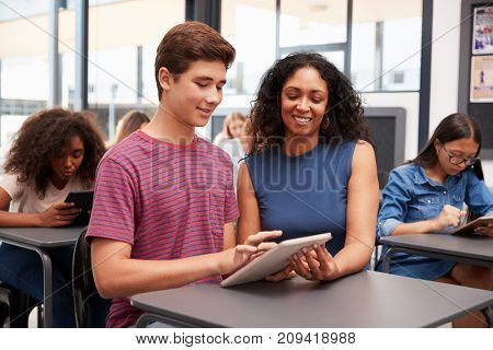 Teacher helping teenage schoolboy with tablet computer
