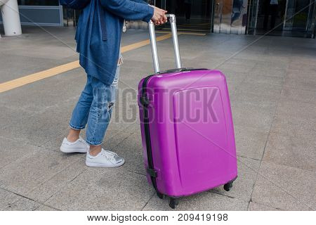 Close up legs of the young woman standing at the airport with a suitcase